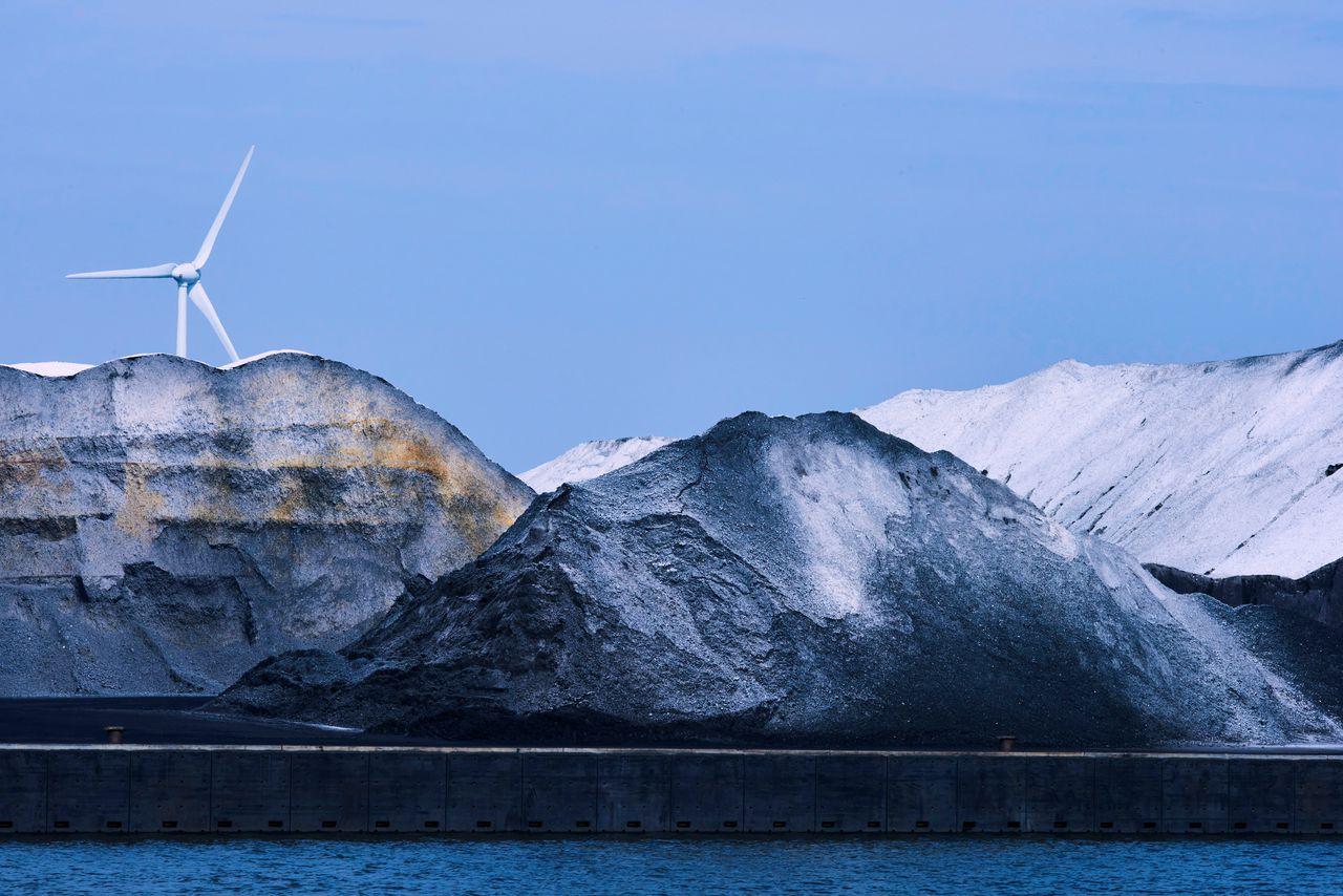 Bergen steenkool in de haven van Amsterdam. Op de achtergrond een windmolen. Foto Nico Garstman/ANP